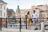 Urban people street lifestyle - couple of tourists on travel or smart casual modern young professionals talking in Stockholm city, Sweden.