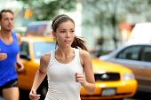 Active people jogging on New York city street, NYC. Young asian female runner and caucasian man running together training in Manhattan busy traffic with yellow taxi cabs in summer.