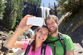 Active lifestyle couple of hikers hiking at Yosemite National Park taking a self-portrait picture with smartphone by waterfall, Vernal Fall. Young hiking couple relaxing in summer nature landscape.