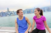 Runners relaxing after workout in Hong Kong city. Running caucasian and asian man and woman post run taking a break talking together on the Avenue of the Stars in Victoria harbor, HongKong Skyline.