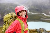 stock photo of rain  - Hiker woman hiking with backpack in rain on trek living healthy life - JPG
