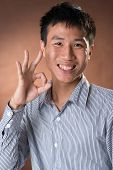 Young Chinese frank businessman give you an Okay gesture, closeup portrait in studio.