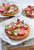 Toasts with dried tomatoes, pepperoni and ricotta
