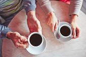 pic of hot couple  - Porcelain cups with hot arabica held by young couple - JPG