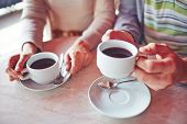 Porcelain cups with hot coffee held by young man and woman