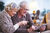 stock photo of wifes  - Elderly husband and wife with touchpad networking at leisure - JPG