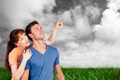Happy couple looking upwards against green grass under grey sky
