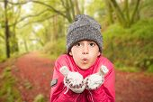 Wrapped up little girl blowing over hands against peaceful autumn scene in forest