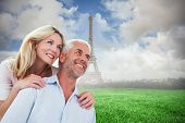 Smiling couple embracing and looking against eiffel tower