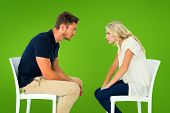 Young couple sitting in chairs arguing against green vignette