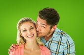 Handsome man kissing girlfriend on cheek against green vignette