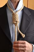 Businessman adjusting a hangman noose instead of a tie .Businessman hangman adjusting a noose rope like tie.