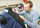 stock photo of tailoring  - young male tailor portrait in workshop - JPG