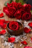 Red rose with roses in bowl with pile of salt ,stones on old wooden board