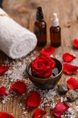 Red rose in bowl with pile of salt ,stones ,towel,oil on old wooden board