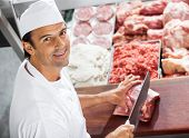 picture of slaughterhouse  - High angle portrait of confident butcher cutting meat at counter in butchery - JPG
