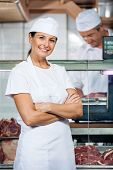 Portrait of confident female butcher with male colleague working in store
