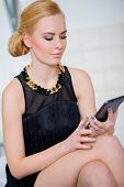 Close up Gorgeous Woman in Stylish Black Dress Using Her Tablet