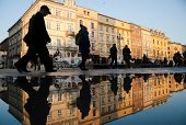 People are reflecting in the water as they pass by central square in Krakow's old town