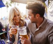 picture of romantic  - romantic couple drinking beer in plastic cups at outdoor bar - JPG