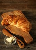 Fresh homemade croissant on a cupboard with butter and wooden knife