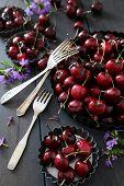 Fresh summer cherries and flowers in aluminum plates