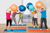 stock photo of pilates  - Happy Multiethnic People Standing On Exercising Mat Lifting Pilates Ball - JPG