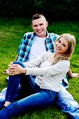 Young beautiful couple in love lying on the grass