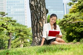 stock photo of japan girl  - Asian business woman reading using tablet app in Tokyo - JPG