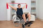 picture of handicapped  - Handicapped Man On Wheelchair Exercising With Resistance Band At Home - JPG