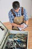 picture of fuse-box  - Electrician Looking At Fuse Box Holding Clipboard - JPG
