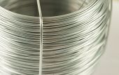 stock photo of coil  - Macro closeup image of light grey metal texture coil of soft fictile pliable tin wire in cylindrical shape