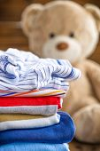 pic of baby bear  - Baby clothes stack and teddy bear on a wooden table - JPG