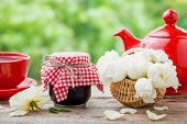 foto of bunch roses  - Red teapot jars of jam basket with roses bunch and tea cup - JPG