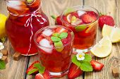 stock photo of cold drink  - Cold strawberry drink with fresh strawberries and lemon on wooden background - JPG
