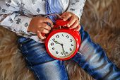 picture of little boys only  - A little boy holding a big red clock waiting for miracles - JPG