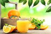 stock photo of wooden crate  - Glass of orange juice with oranges in crate on wooden table and natural background - JPG