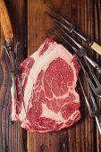 stock photo of ribeye steak  - raw beef Ribeye  steak   on wooden  table with vintage carving forks - JPG
