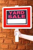 foto of yard sale  - Wooden Yard Sale sign in female hand on red brick wall background - JPG