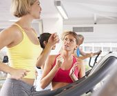 foto of encouraging  - Woman On Running Machine In Gym Encouraged By Personal Trainer - JPG