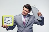 stock photo of disappointment  - Disappointed businessman holding folders and clock over gray background - JPG