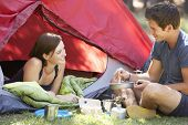 foto of breakfast  - Young Couple Cooking Breakfast On Camping Holiday - JPG