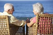image of couple sitting beach  - Senior Couple Sitting In Chairs Relaxing On Beach - JPG