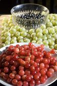 stock photo of black-cherry  - Bowls of red cherries and black currants surrounded by green gooseberries on a wooden chopping board  - JPG
