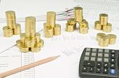 picture of piles  - Pencil and calculator with pile of gold coins as tower on finance account have pile of paperwork as background - JPG
