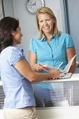 stock photo of receptionist  - Female Patient With Receptionist In Doctors Waiting Room - JPG