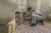 stock photo of convection  - pipefitter installing system of heating - JPG