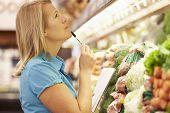 stock photo of supermarket  - Woman Reading Shopping List In Supermarket - JPG