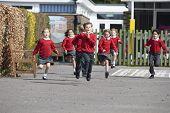 foto of playground school  - Elementary School Pupils Running In Playground - JPG