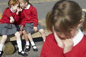 picture of school bullying  - Female Elementary School Pupils Whispering In Playground - JPG